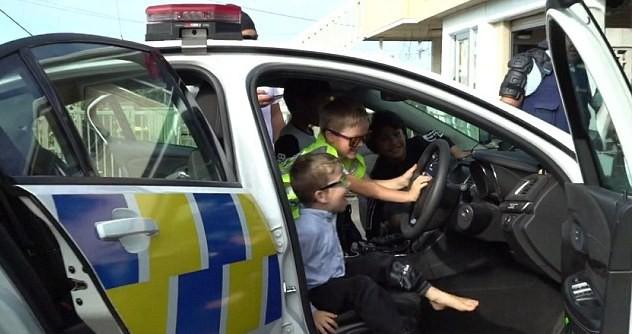 Cậu bé và các bạn được cho ngồi vào xe cảnh sát